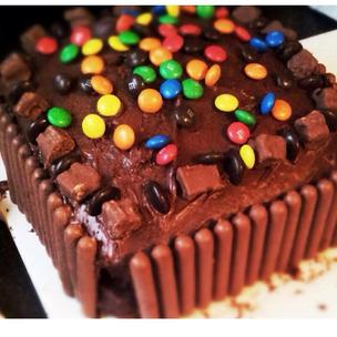 A giant delicious chocolate cake covered with wispa, m&m's, chocolate fingers and minstrels, enough to serve for the whole world!