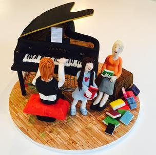 Tim Minchin playing the Grand Piano for Matilda and Miss Honey posed on a box of books, taken from the original Roal Dahl scence - All figures and props made from scratch with sugar/flower modelling paste. The cake (grand piano and cardboard box) is rhubarb and custard with a cream cheese frosting, I decided to go old school with the theme! Many hours of hard work, but pretty chuffed with the outcome.